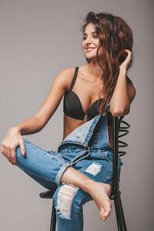 Porträt der sexy schönen frau in den jeans insgesamt. nettes attraktives hipster-mädchen, das auf stuhl sitzt. model posiert im studio