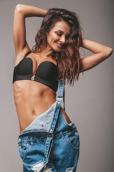Porträt der sexy schönen frau in den jeans insgesamt. nettes attraktives hipster-mädchen, das im studio aufwirft