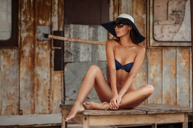 Porträt der sexy schönen gebräunten frau, die im modebadebekleidungsbikini, im hut und in der sonnenbrille an der seeküste aufwirft. ebody.