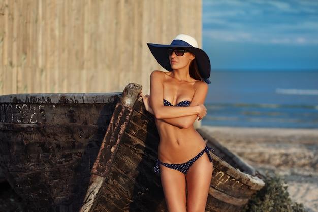 Porträt der sexy schönen gebräunten frau, die im modebadebekleidungsbikini, im hut und in der sonnenbrille an der seeküste aufwirft.