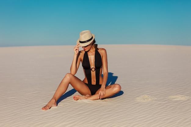 Porträt der sexy schönen gebräunten modellfrau, die in der mode schwarzen bikini, hut und sonnenbrille auf sandstrand aufwirft