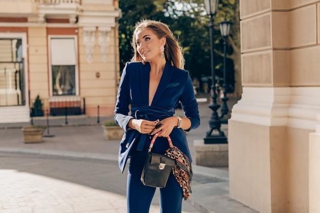 Porträt der sexy stilvollen frau, die in der straße im blauen anzug am sonnigen herbsttag geht