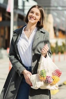 Porträt der smiley-frau, die einkaufstüten hält
