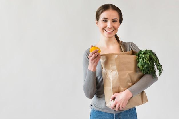 Porträt der smiley-frau, die papiertüte mit lebensmitteln hält