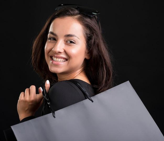 Porträt der smiley-frau, die schwarze tasche hält