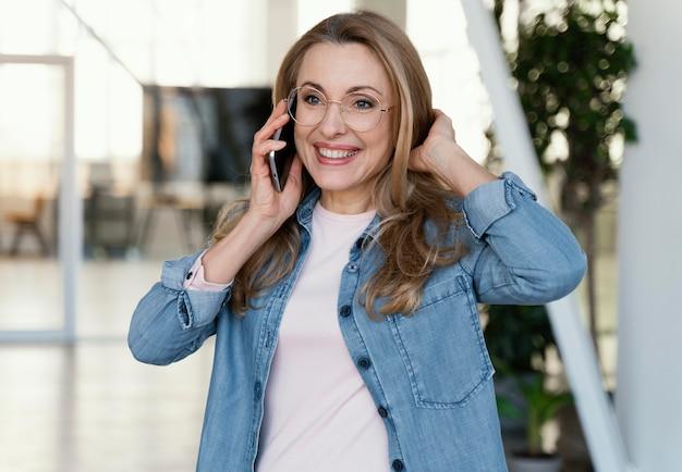 Porträt der smiley-geschäftsfrau, die am telefon spricht