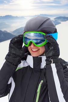 Porträt der snowboarderfrau auf der schönen landschaft des hintergrunds der schneebedeckten hohen berge