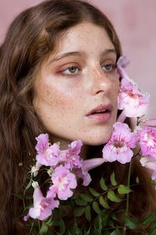 Porträt der sommersprossigen frau, die eine rosa blume gegen ihr gesicht hält
