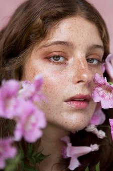 Porträt der sommersprossigen frau, die eine rosa blume hält