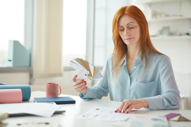 Porträt der sommersprossigen frau, die farbfelder beim erstellen des modedesigns am arbeitsplatz hält, kopieren raum