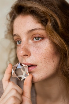 Porträt der sommersprossigen frau, die ihren mund mit kristall bedeckt