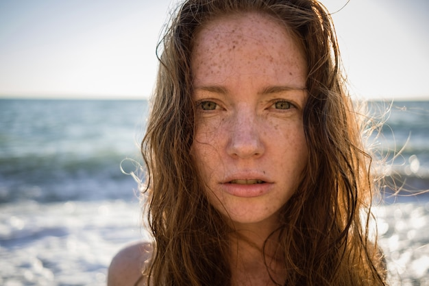 Porträt der sommersprossigen schönen frau am sonnenuntergangsstrand