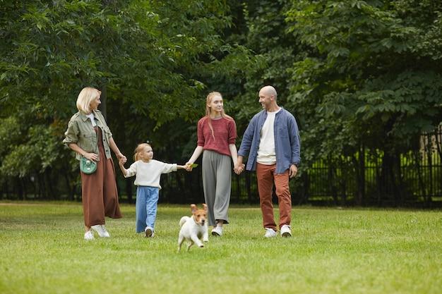 Porträt der sorglosen familie mit zwei kindern und hund, die hände beim gehen auf grünem gras im freien halten
