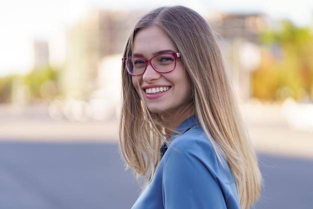 Porträt der sorglosen jungen frau, die mit städtischer straße lächelt. fröhliches kaukasisches mädchen, das brillen in der stadt trägt.