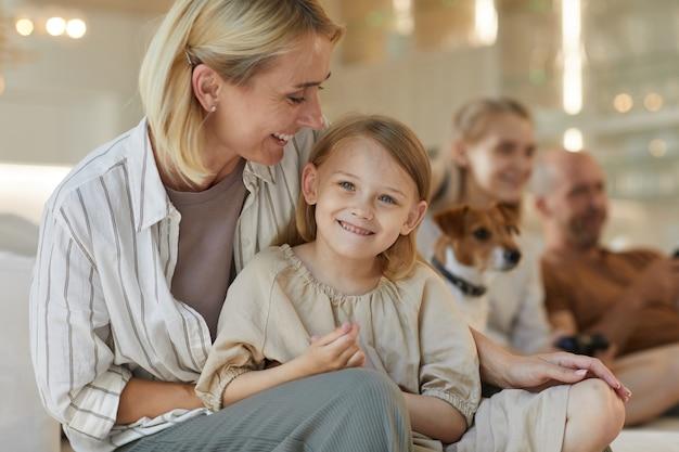 Porträt der sorglosen jungen frau, die niedliche tochter umarmt, während sie im innenraum mit familie aufwirft
