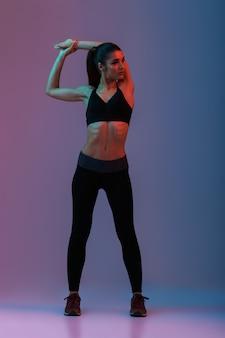 Porträt der sportlerin in voller länge in schwarzer fitnesskleidung, die beiseite schaut, während sie sich aufwärmt und ihre arme streckt, lokalisiert über bunte wand