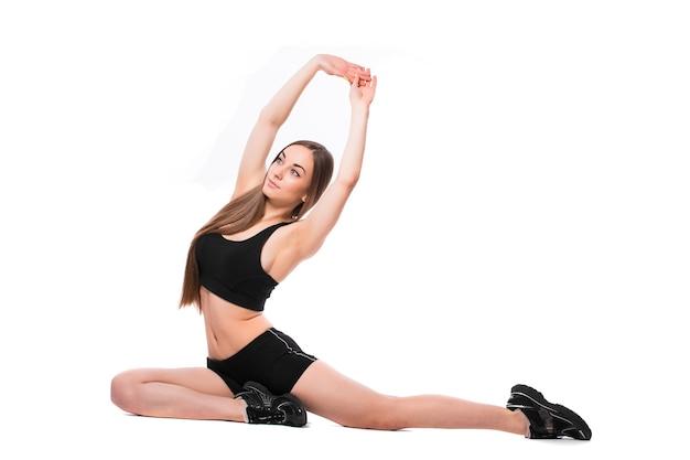 Porträt der sportlichen fit frau in der sportbekleidung, die übungen macht, die auf weißem hintergrund lokalisiert werden