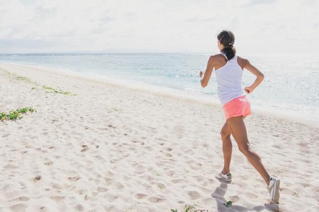 Porträt der sportlichen frau, die am strand joggt