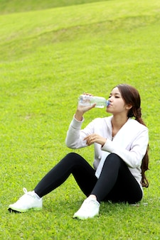 Porträt der sportlichen frau, die auf dem gras sitzt und erfrischung nach dem training mit copyspace erhält