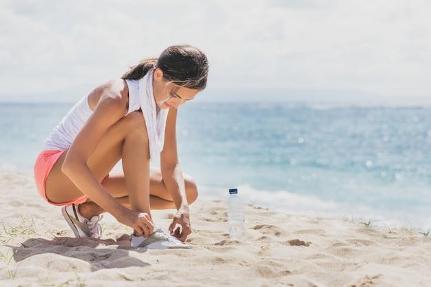 Porträt der sportlichen frau, die ihre schnürsenkel am strand bindet