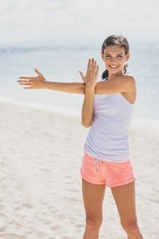 Porträt der sportlichen frau, die lächelt, während arme sich am strand strecken