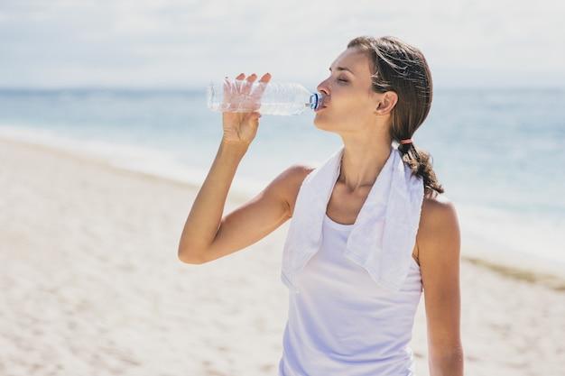 Porträt der sportlichen frau, die mineralwasser nach dem training am strand trinkt