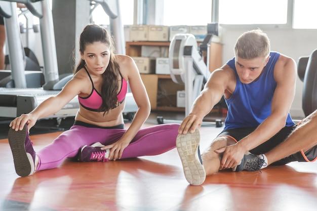 Porträt der sportlichen frau und des mannes, die beinstreckung im fitnessstudio tun