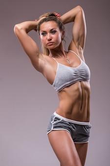 Porträt der sportlichen jungen frau mit dem muskulösen körper, der gegen einen grauen hintergrund aufwirft