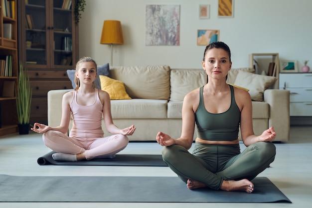 Porträt der sportlichen mutter und der jugendlichen tochter, die mit gekreuzten beinen sitzen, während meditation zusammen zu hause praktizieren