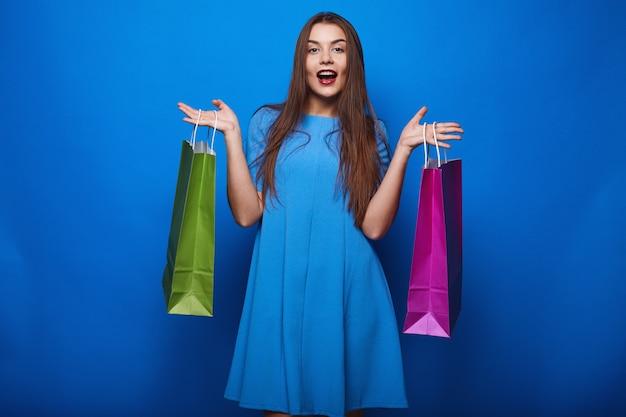 Porträt der stilvollen frau des modezaubers mit einkaufstaschen