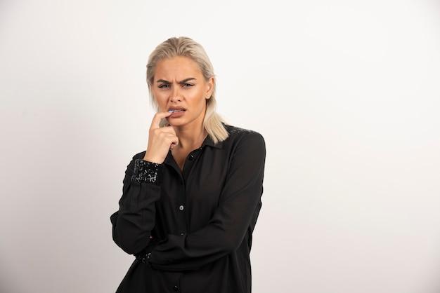 Porträt der stilvollen frau im schwarzen hemd, das auf weißem hintergrund aufwirft. hochwertiges foto