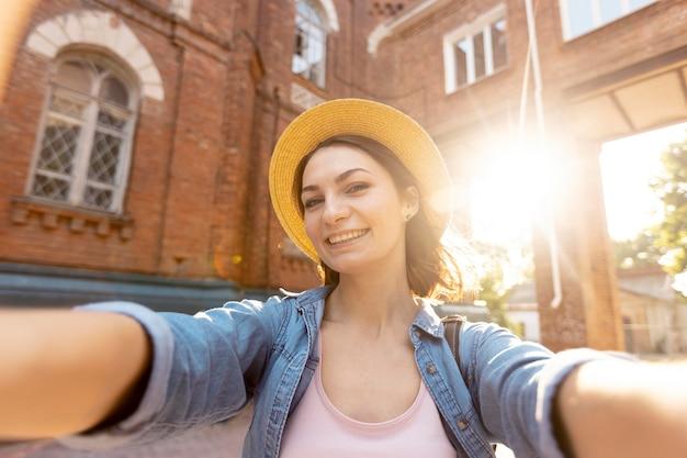 Porträt der stilvollen frau mit hut, der ein selfie nimmt