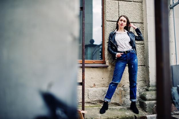 Porträt der stilvollen jungen frau, die auf lederjacke und zerrissenen jeans an den straßen der stadt trägt