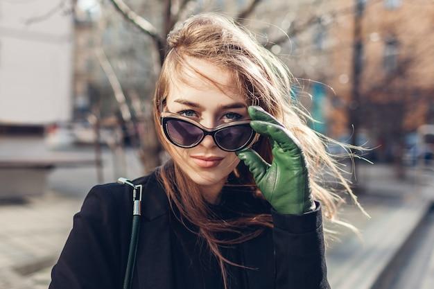Porträt der stilvollen jungen frau, die sonnenbrille und handschuhe trägt