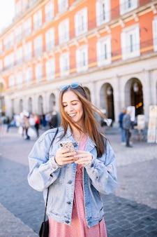 Porträt der stilvollen lächelnden glücklichen jungen frau in der straße mit den perfekten weißen zähnen, die ihr mobile schauen.
