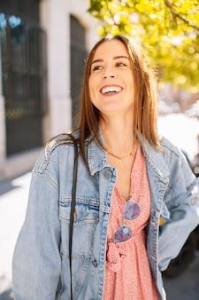 Porträt der stilvollen lächelnden glücklichen jungen frau in der straße mit den perfekten weißen zähnen. sommer- und frühlingsmodetrend, jeansjacke, sonnenbrille, fröhlich, positiv, lachend. lebensstile.