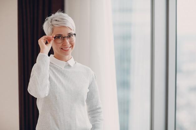 Porträt der stilvollen lächelnden jungen frau im weißen pullover und in den gläsern