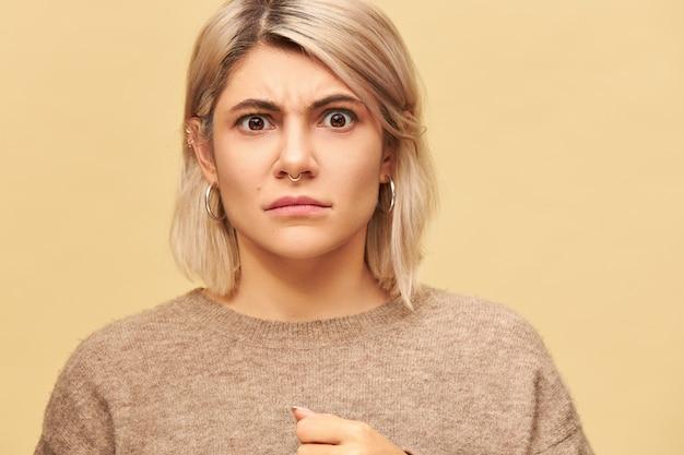 Porträt der stilvollen launischen wütenden jungen kaukasischen frau, die gesichtspiercing und warmen pullover mit gerunzelter stirnbrauen trägt, die schlecht gelaunt sind und ihre missbilligung und unzufriedenheit demonstrieren. negative emotionen