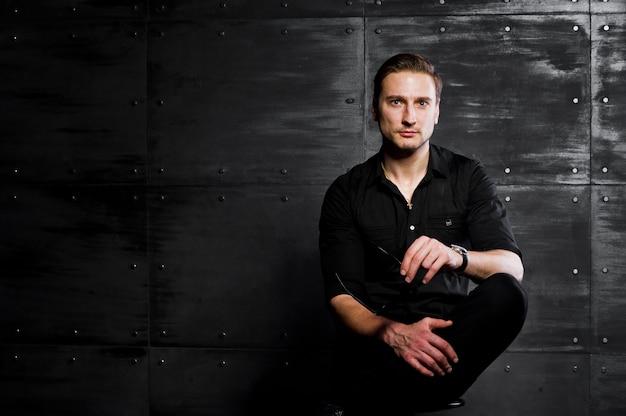 Porträt der stilvollen mannabnutzung auf schwarzem hemd gegen stahlwand.