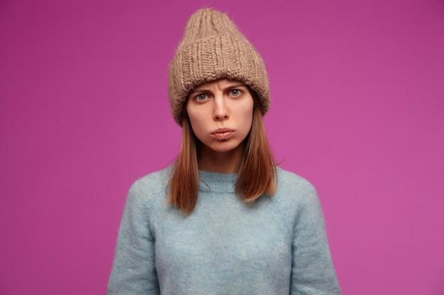 Porträt der stirnrunzeln, junge frau mit brünetten langen haaren. trägt einen blauen pullover und eine strickmütze.