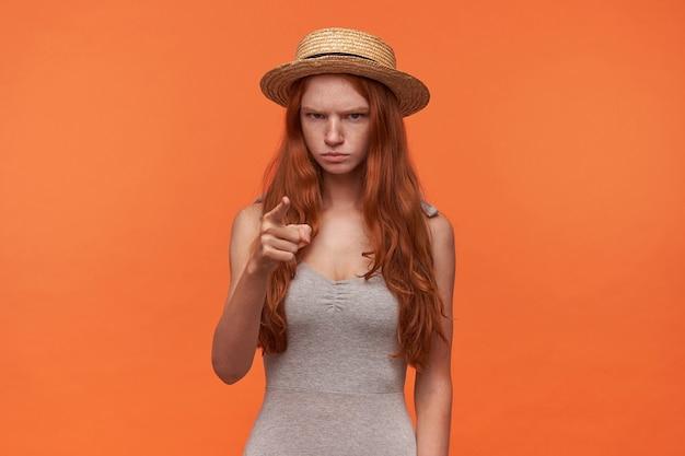Porträt der stirnrunzelnden jungen rothaarigen frau mit dem langen haar, das graues hemd und strohhut trägt, zeigefinger im warnzeichen erhebend, über orange hintergrund aufwerfend