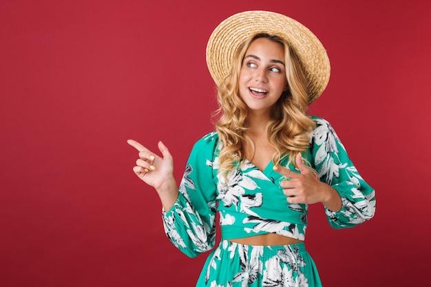 Porträt der süßen fröhlichen lächelnden jungen schönen blonden süßen frau im kleid, die isoliert über der roten wand posiert