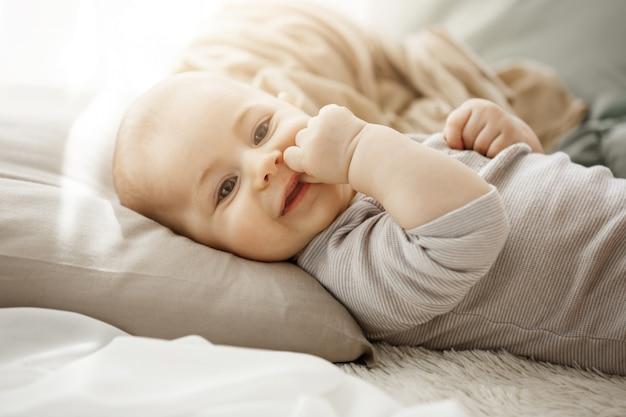 Porträt der süßen lächelnden neugeborenen tochter, die auf gemütlichem bett liegt. kind schaut in die kamera und berührt das gesicht mit ihren kleinen händen. momente der kindheit.