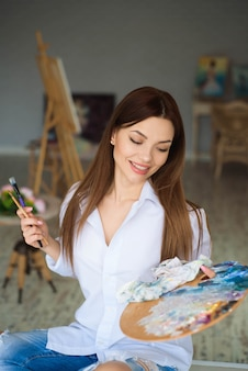 Porträt der talentierten jungen frau, die bild im kunststudio mit inspiration malt
