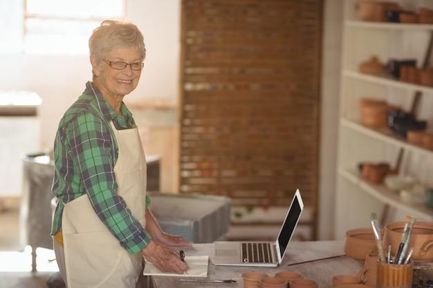 Porträt der töpferin, die notiz vom laptop macht