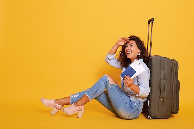 Porträt der touristenfrau, die auf flug wartet und auf boden in der nähe ihres koffers sitzt,