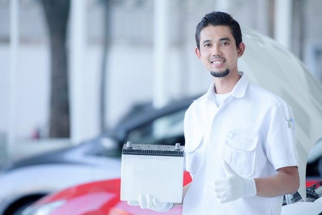 Porträt der tragenden autobatterie des männlichen mechanikers in der werkstatt