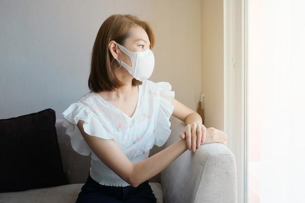Porträt der tragenden gesichtsmaske der jungen asiatin, die nahe fenster sitzt