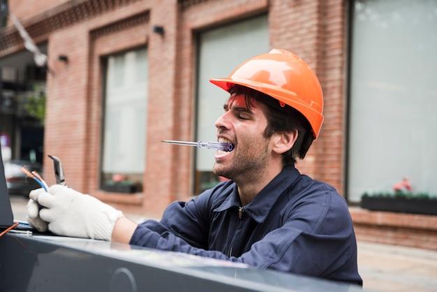 Porträt der tragenden prüfvorrichtung des männlichen elektrikers im mund beim arbeiten