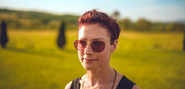 Porträt der tragenden sonnenbrille der frau, die im freien steht
